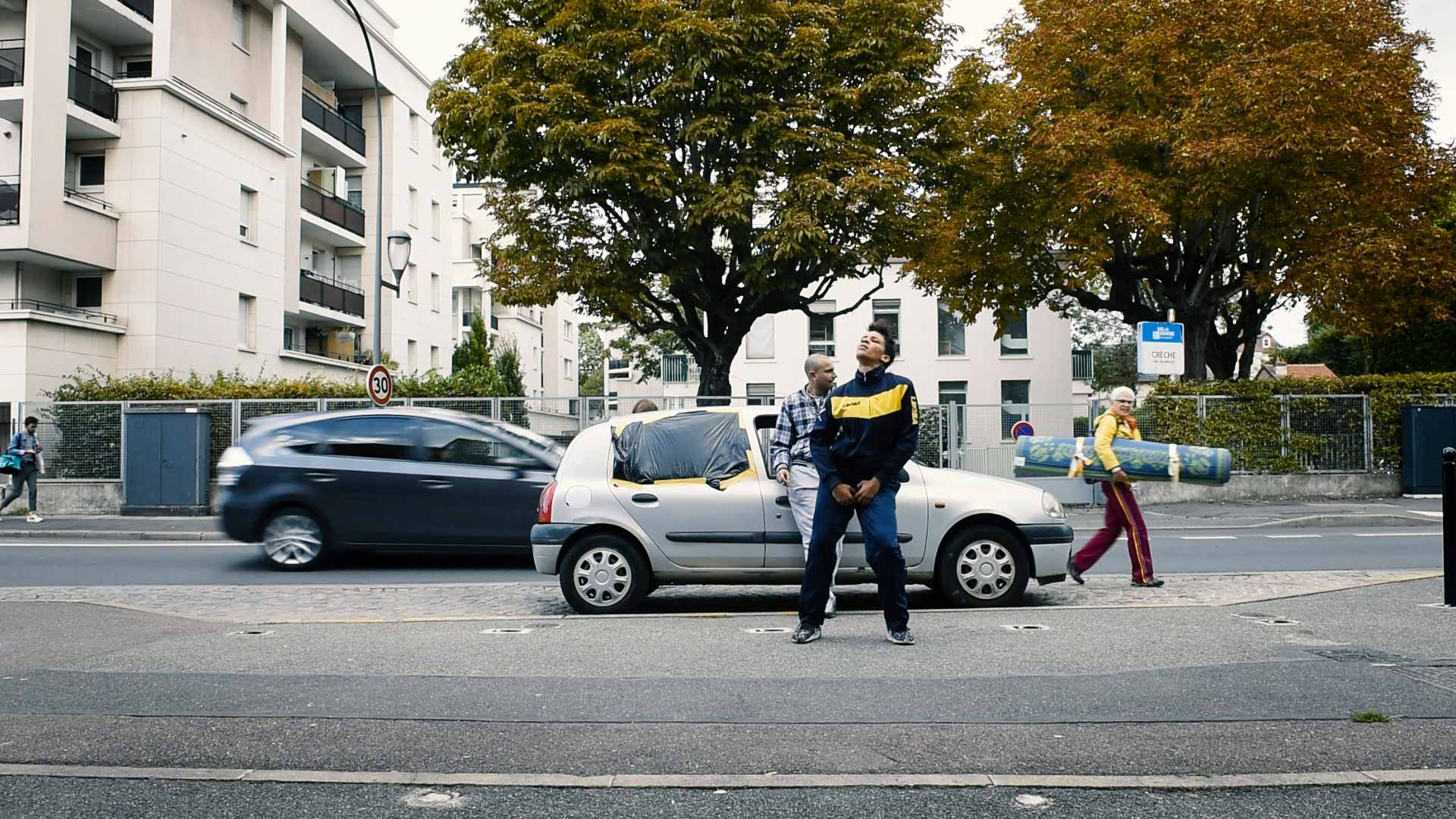 En dansare står framför en vandaliserad bil på en gata
