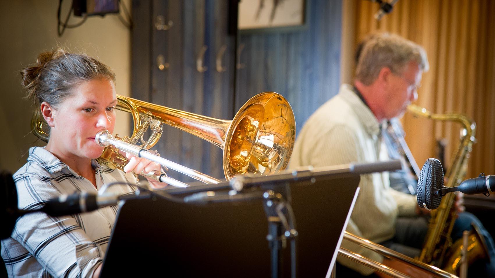 Ingrid sitter i studion och spelar trombon.