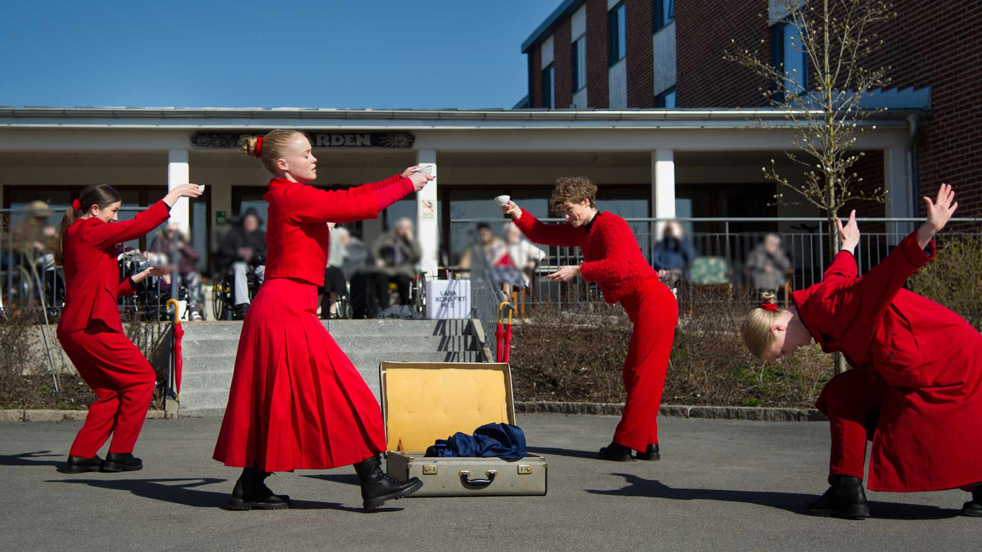 Rödklädda dansare utanför ett äldreboende