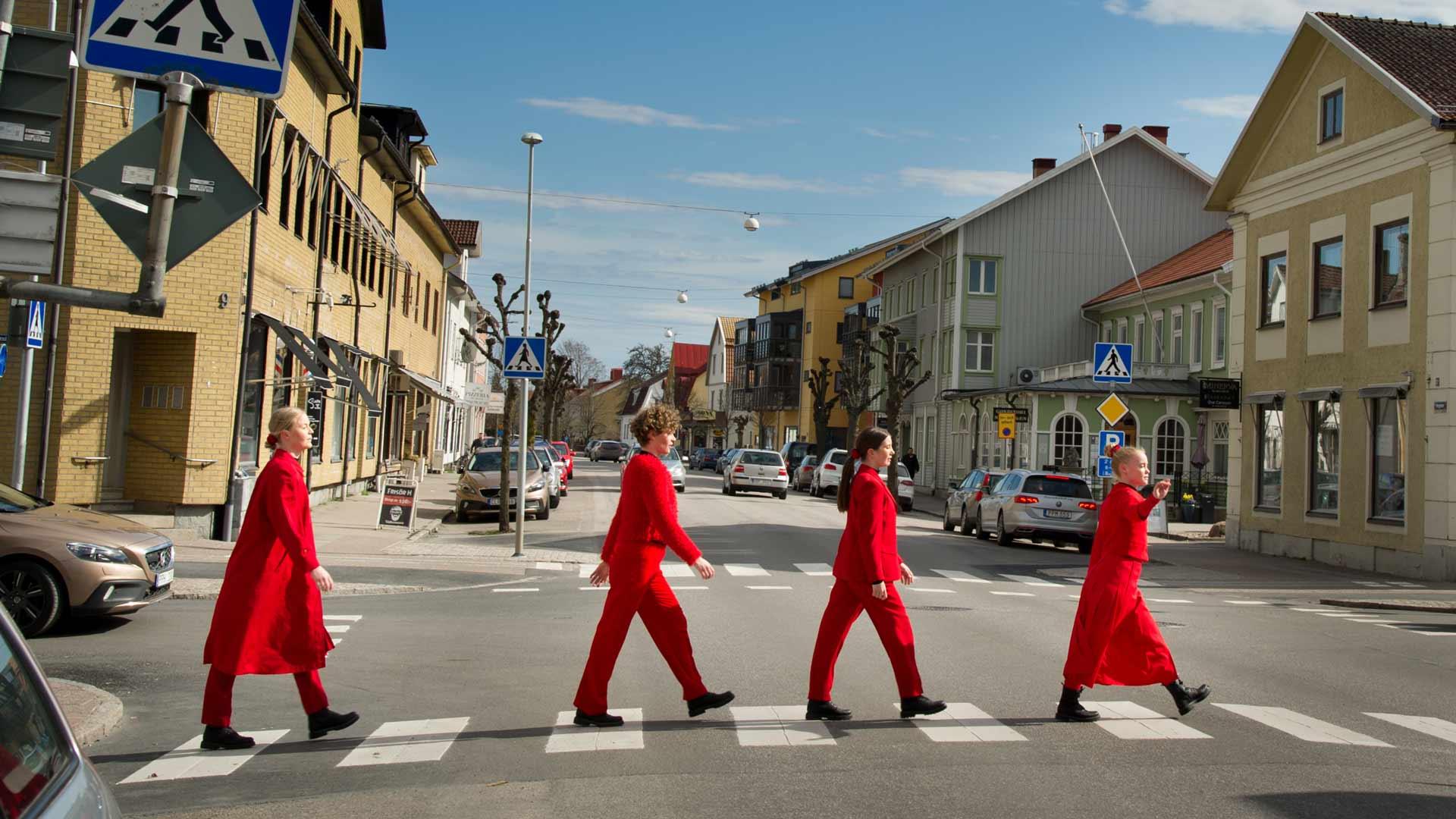 Fyra rödklädda dansare går över ett övergångsställe i Vara