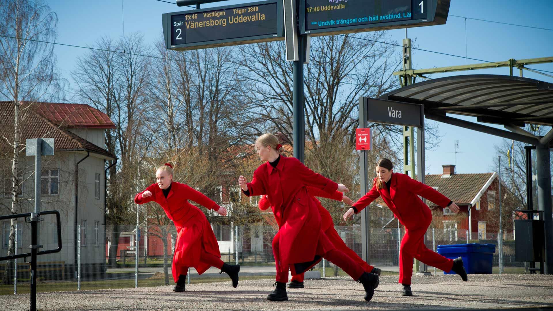 Fyra rödklädda dansare på stationsperrongen i Vara