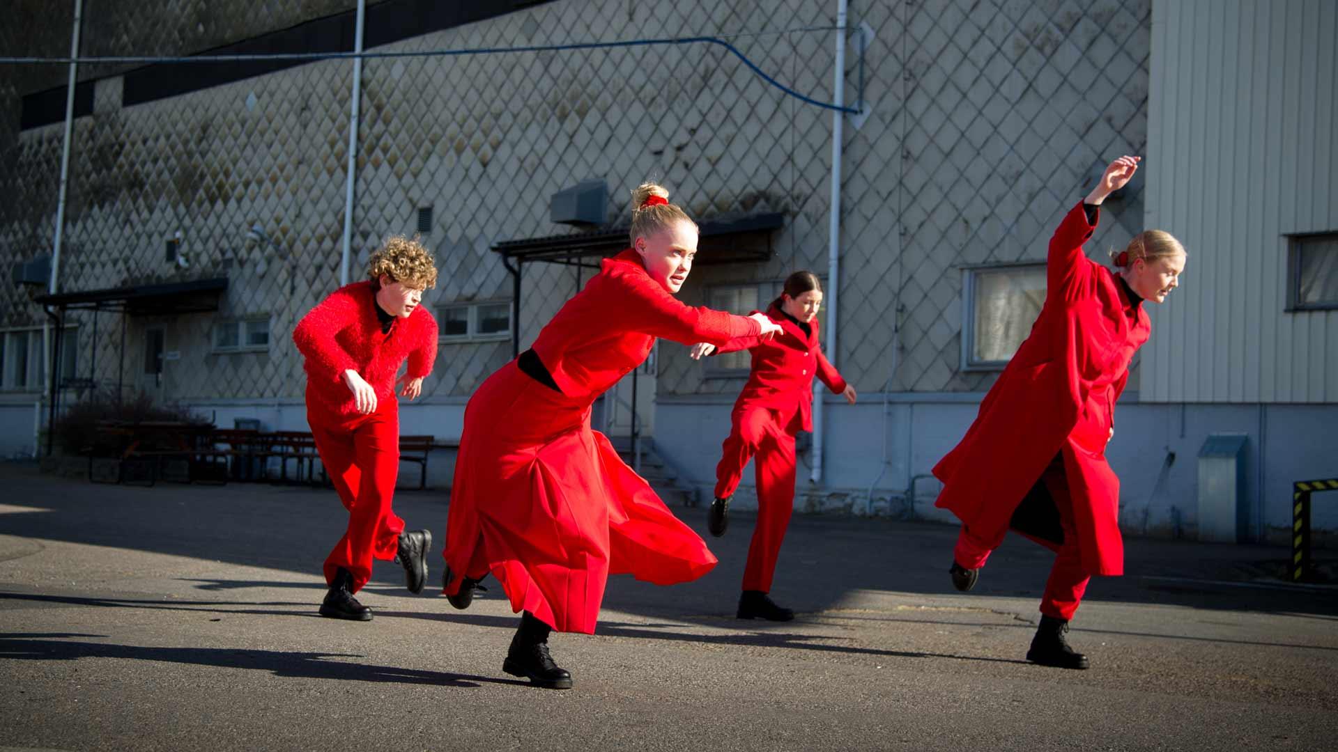 Fyra rödklädda dansare i en rå industrimiljö