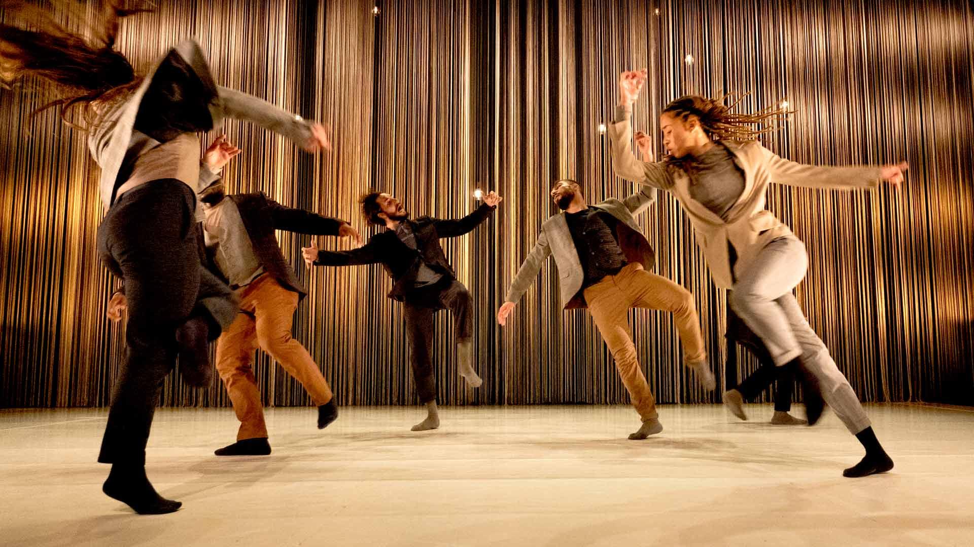 Fem dansare rör sig på en scen