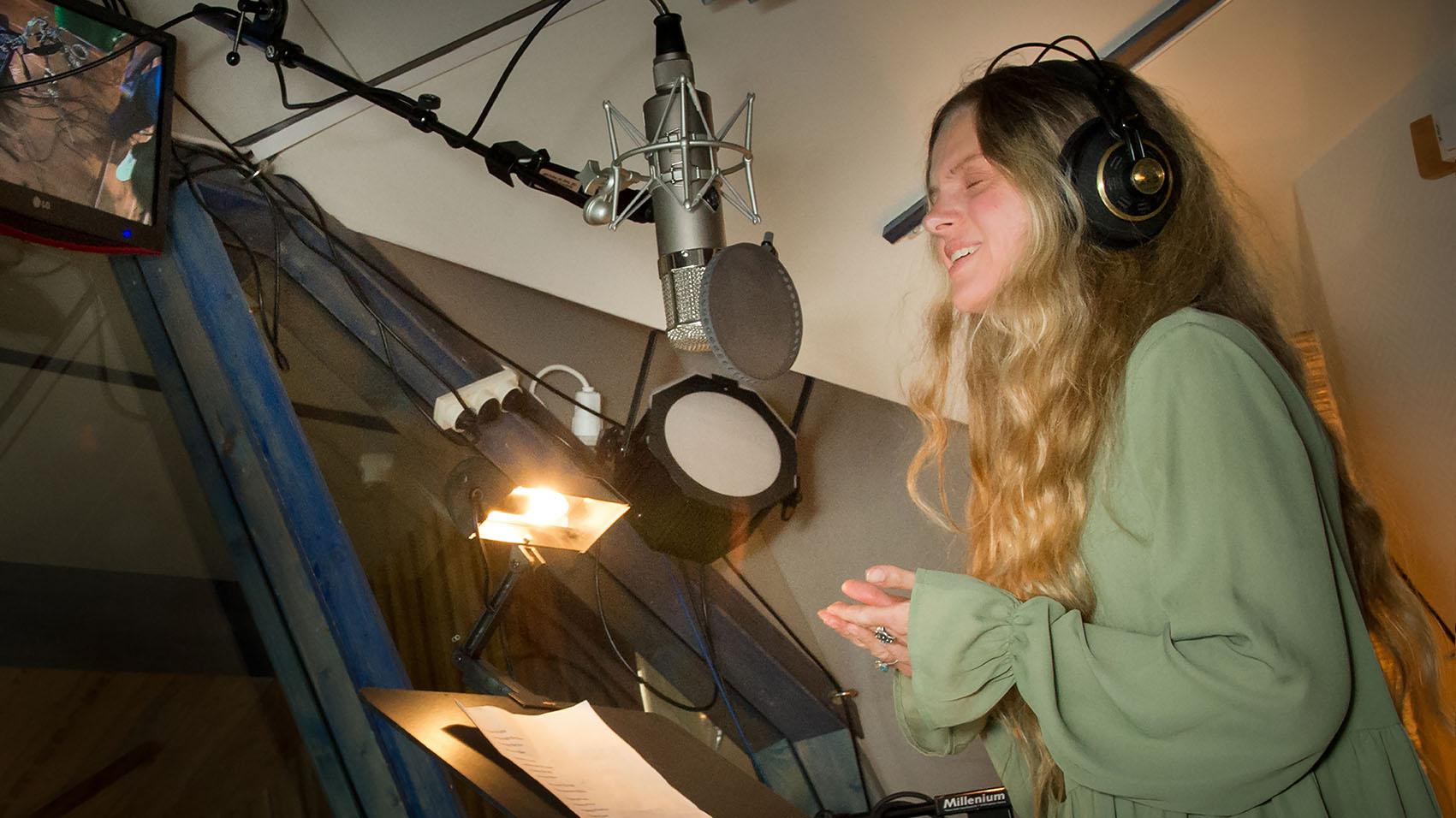 Maria står i studion och sjunger i en mikrofon.