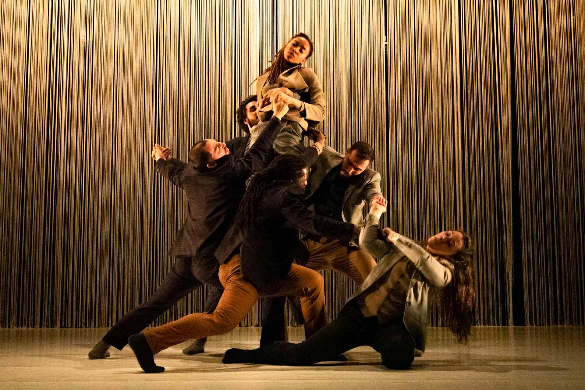 Sex dansare med kläder i beige och bruna toner.
