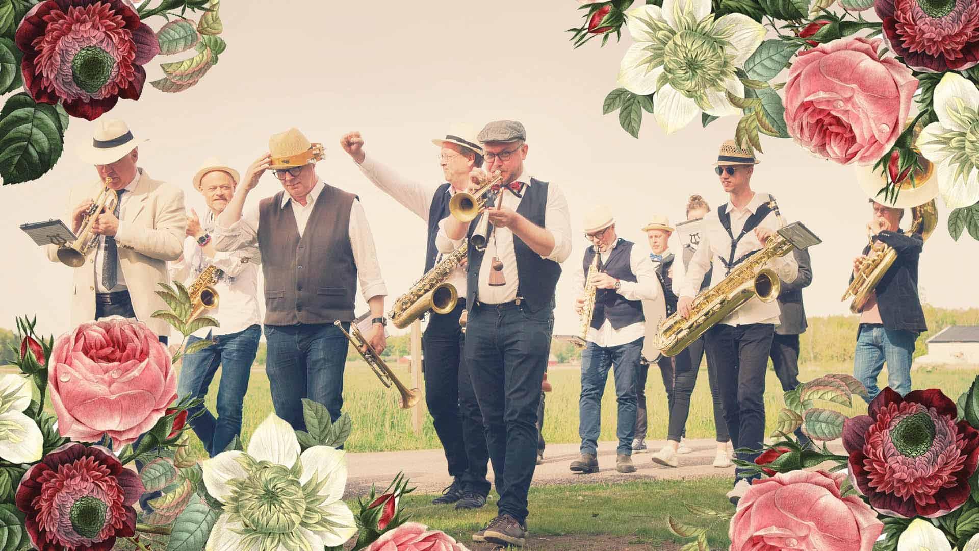 Musiker i Bohuslän Big Band går på en grusväg och spelar sina instrument