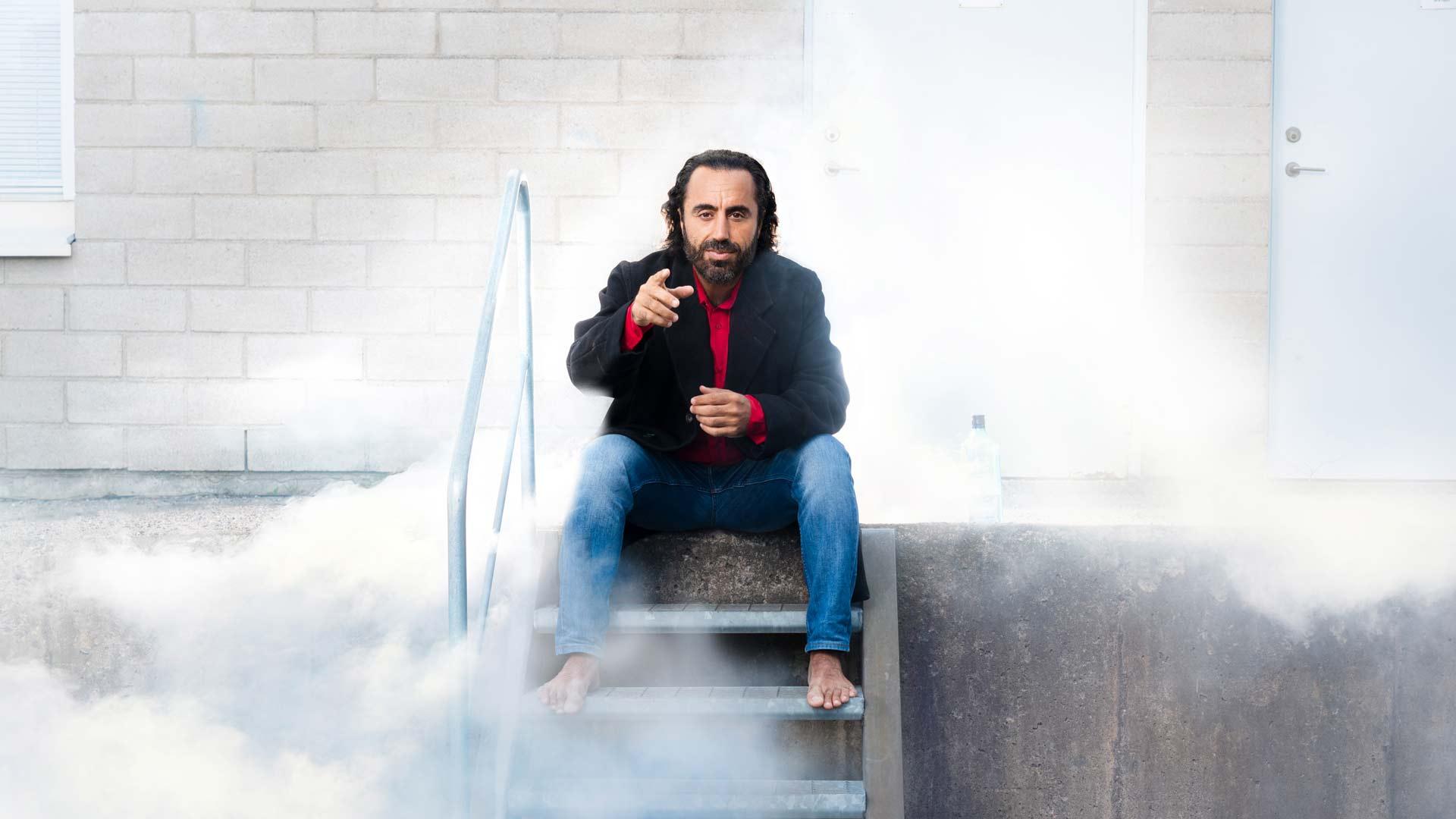 Özz Nûjen sitter på en metalltrapa omgiven av vit rök