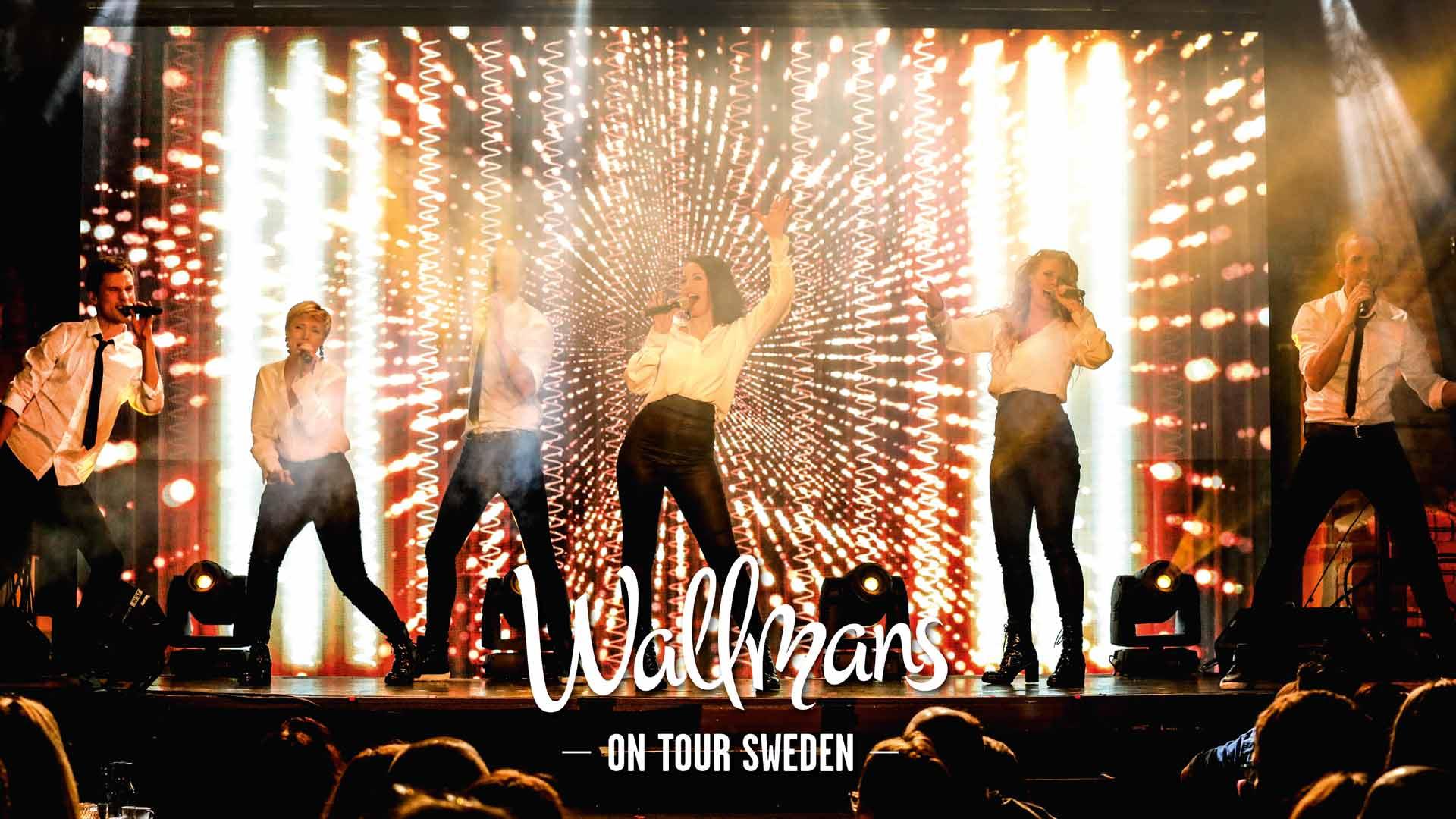 Showartister står på scen framför en ljusvägg