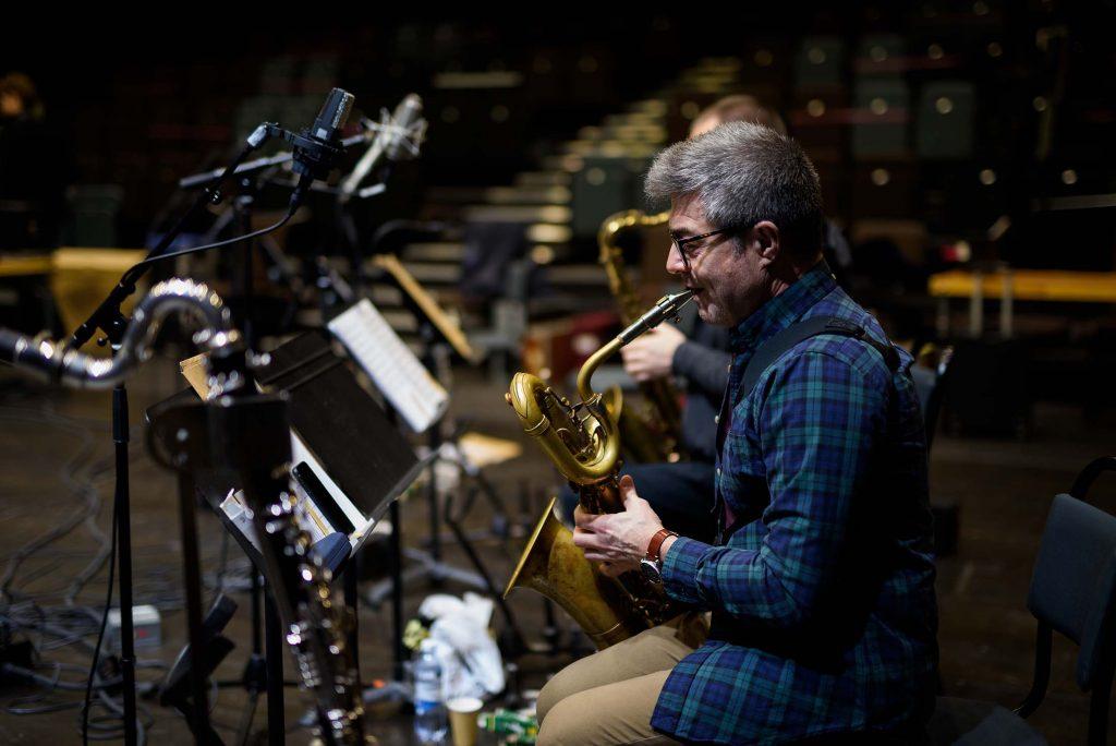 Alberto Pinton som spelar barytonsaxofon sittandes vid inspelningsutrustning