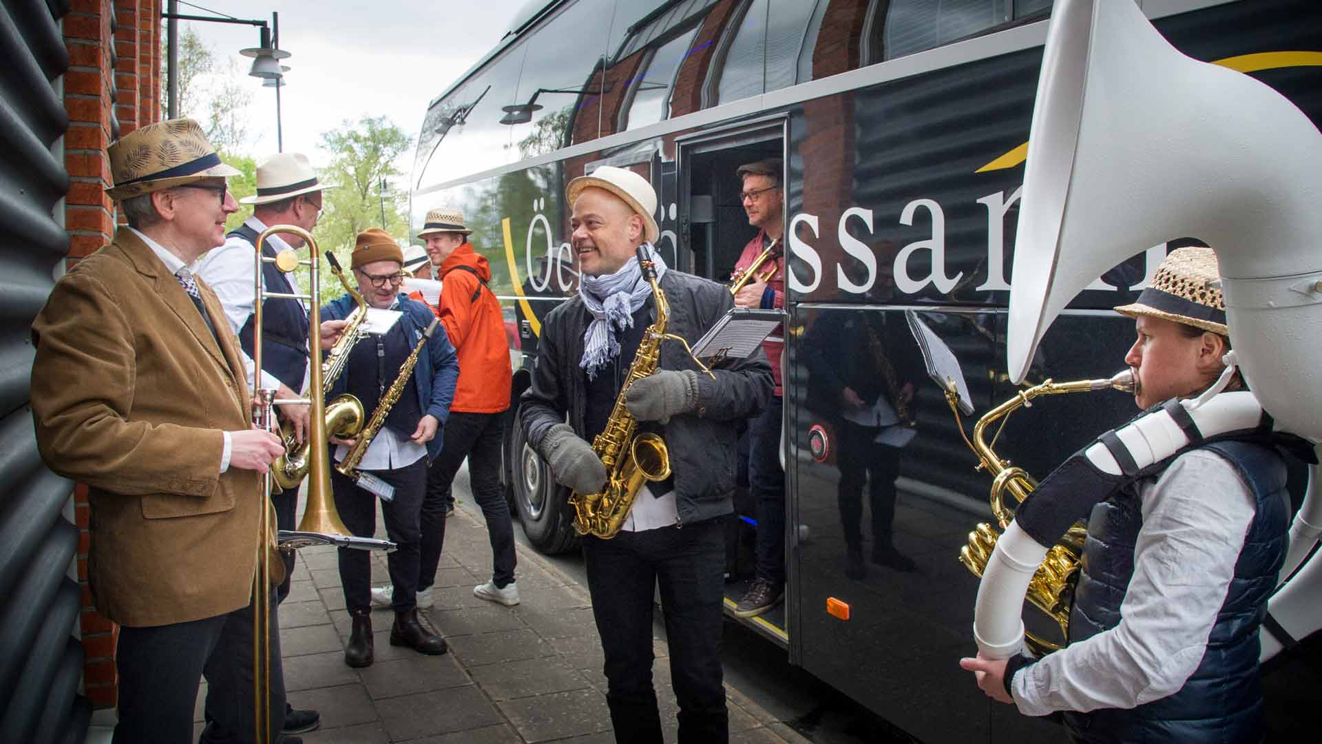 Musiker ur storbandet står utanför turnébussen