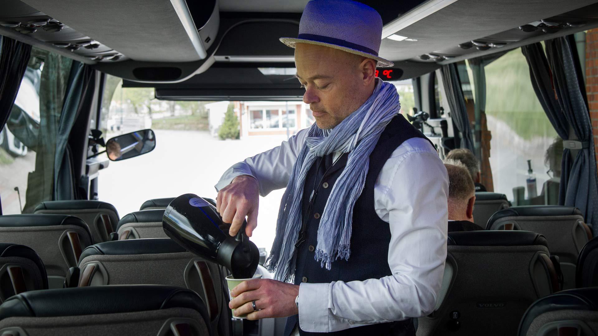 Joakim dricker en kopp kaffe i turnébussen
